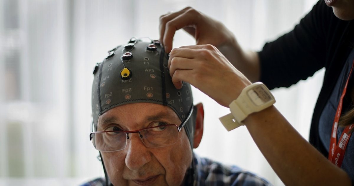 Physiotherapist Vanessa Buhlmann places electrodes on the head of patient Jean-Francois Vernetti during a presentation of a brain-machine interface by the Swiss Federal Institutes of Technology of Lausanne (EPFL) on January 23, 2013 in Sion. More than one hundred patients suffering from severe motor impairments have voluntarily participated in the development of non-invasive brain-machine interfaces.</p>