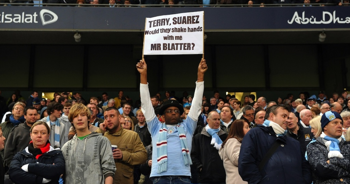 A Manchester City fan displays a banner with a message for FIFA President Sepp Blatter about his handling of recent allegations of racism in football on Nov. 19, 2011.</p>