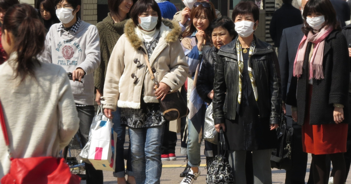 Pedestrians wearing masks walk down a street in the western Japanese city of Fukuoka on March 5, 2013.</p>