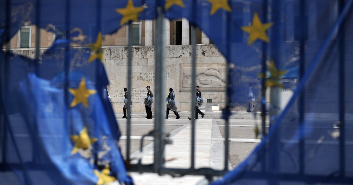Police seen through a burned EU flag in Athens on Wednesday. More politicians are now voicing popular anti-austerity slogans.</p>