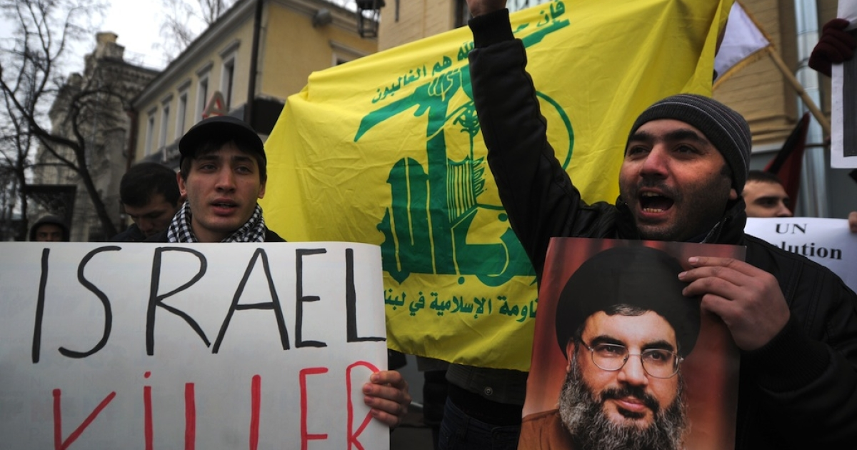 Protestors shout anti-Israel slogans in front of the Israeli embassy holding a portrait of Hezbollah leader Hassan Nasrallah in Moscow on November 21, 2012.</p>