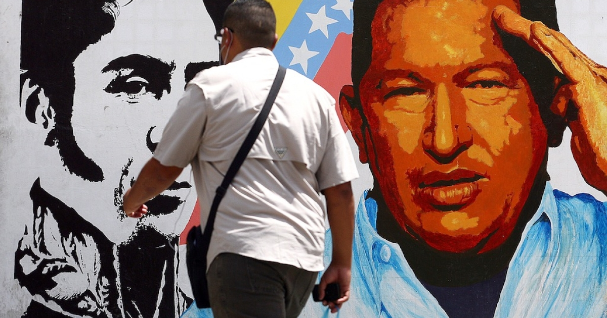 A man walks past a mural portraying the Venezuelan flag, President Hugo Chavez and South American liberator Simon Bolivar at the 23 de Enero neighbourhood, in Caracas on March 5, 2013.</p>
