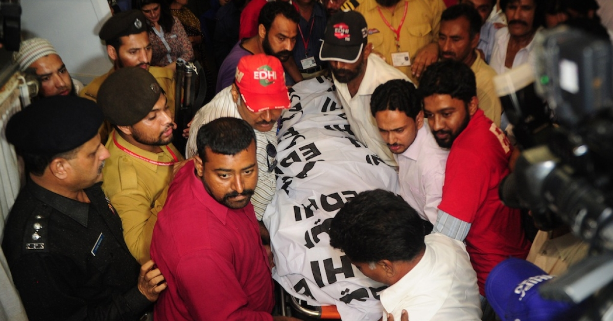 Pakistani rescuers carry the dead body of Zohra Hussain, vice president of the women's wing of Pakistan Tehreek-e-Insaf (PTI) in the province of Sindh, in Karachi on May 18, 2013. Gunmen have killed a Pakistani politician from Imran Khan's party in the southern port city of Karachi on the eve of a partial re-run of May 11 polls that were marked by more than 150 killings.</p>