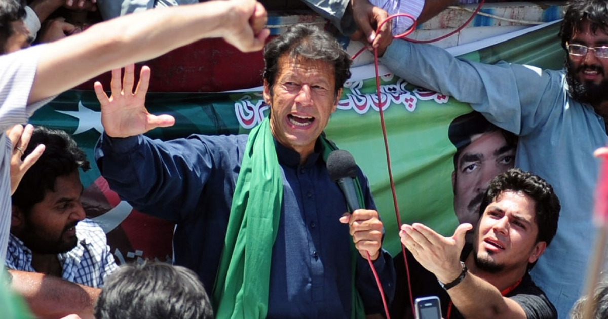 Cricket legend and chairman of Pakistan Tehreek-e-Insaaf (PTI) or Movement for Justice party Imran Khan (C) speaks to supporters during a campaign rally in Karachi on May 7, 2013. Pakistan will elect its new government for the next five years in polls on May 11.</p>