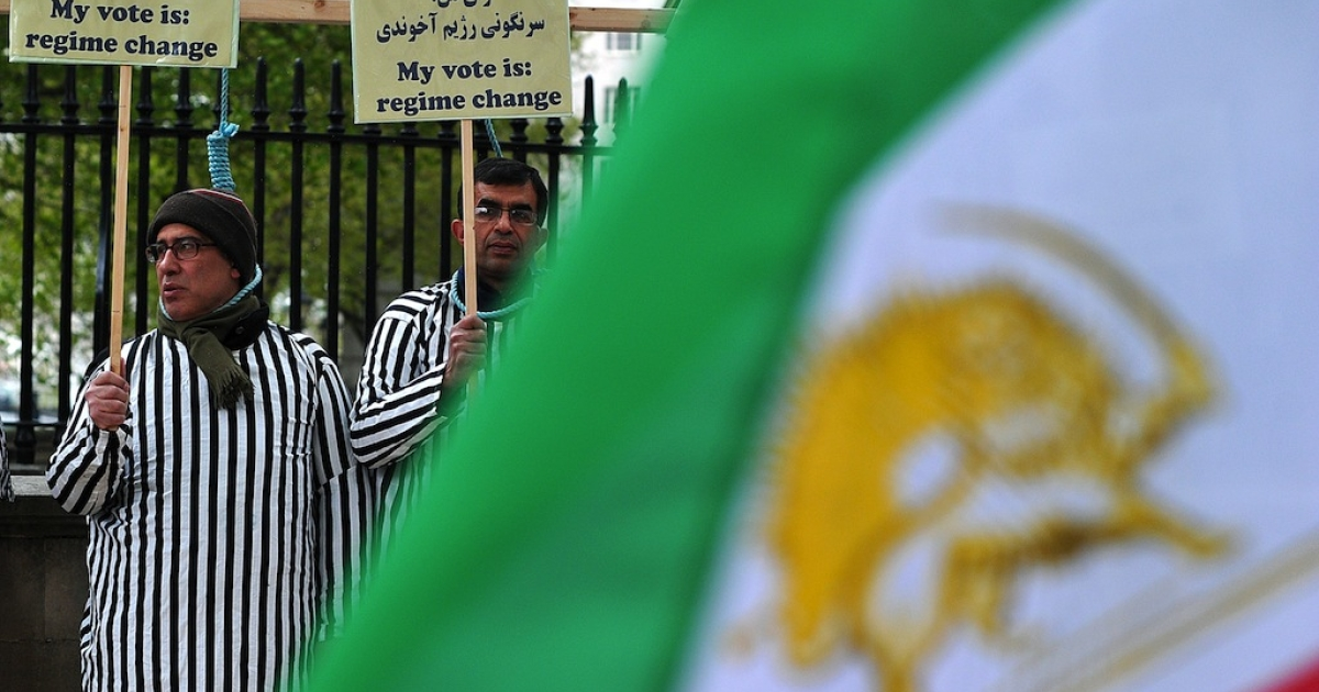 Iranian opposition protesters wearing prisoners' clothing stand through makeshift nooses as they takes part in a rally against the Iranian regime and the upcoming election in central London on May 15, 2013.</p>