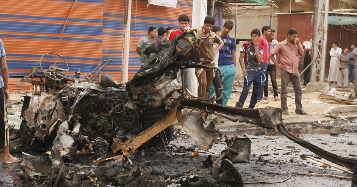 Iraqis look at the remains of a car bomb that detonated in the Kamaliya area of eastern Baghdad on May 20, 2013. A wave of 12 bomb attacks across Iraq killed at least 15 people and wounded dozens more, security and medical officials said.</p>