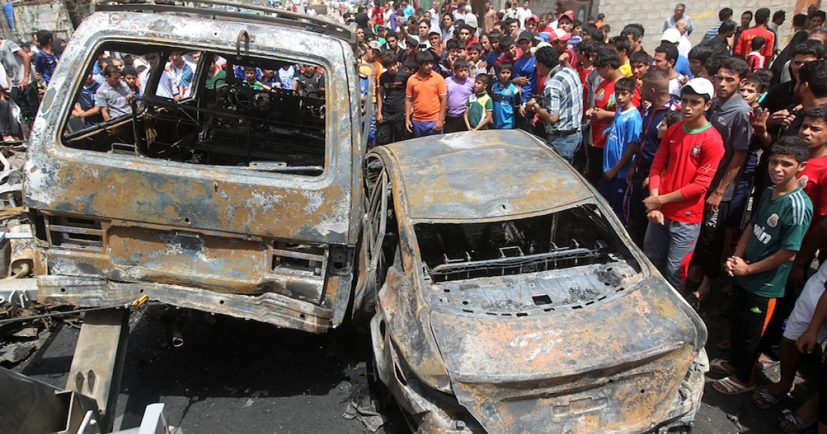 Iraqis gather around burnt vehicles at the site of a car bombing at a market in Baghdad's impoverished district of Sadr City on May 16, 2013 as at least eight people were killed in blasts across the country. Violence in Iraq has fallen from its peak in 2006 and 2007, but attacks remain common, killing more than 200 people in each of the first four months of this year.</p>