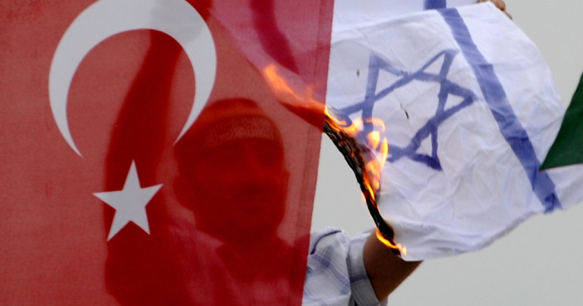 A demonstrator burns an Israeli flag as he sits behind a Turkish flag during a protest against Israel on June 5, 2010 at Caglayan Square in Istanbul. Nine people — eight Turks and a US national of Turkish origin were killed in May 31's pre-dawn raid by Israeli forces on the Turkish ferry, Mavi Marmara, the lead ship in the aid flotilla aiming to break the crippling blockade of Gaza.</p>