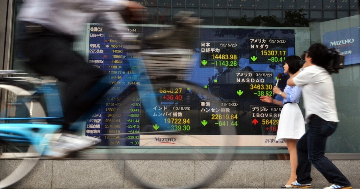 A television journalist reports on the sharp fall in Japanese stocks on May 23, 2013.</p>