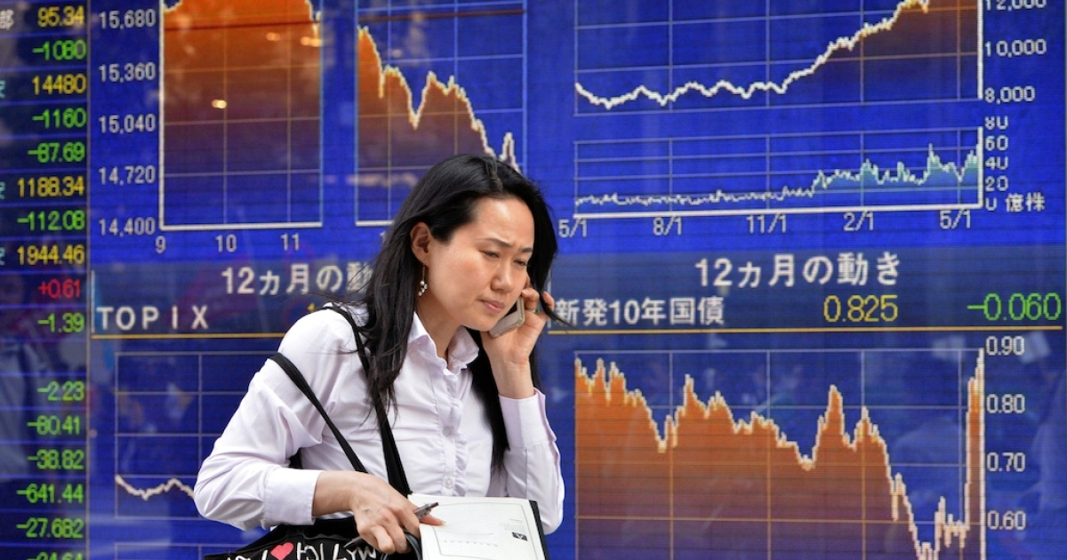 A woman walks past a share prices board in Tokyo on May 23, 2013, the day the Nikkei 225 plunged more than 7 percent.</p>