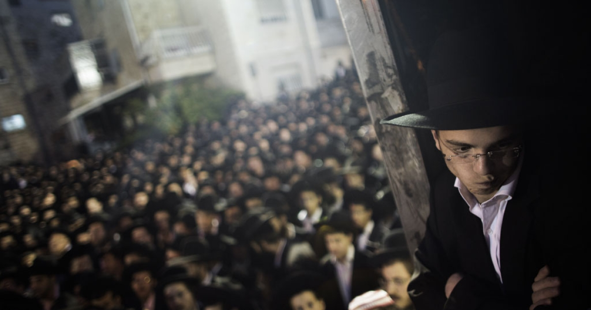 An Orthodox Jew looks on as thousands of others gather in front of the main army recruitment office in Jerusalem on May 16, 2013 to demonstrate against any plans to make them undergo military service, a police spokesman said.</p>