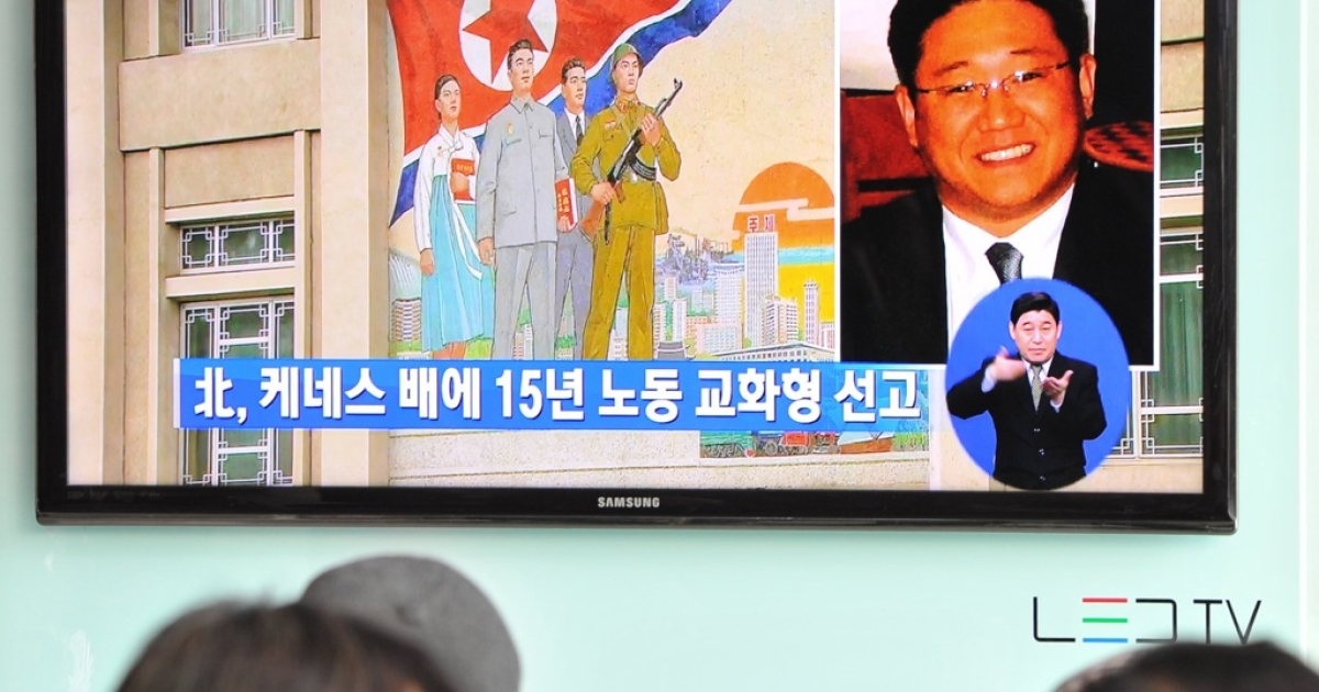 Passersby watch a local television broadcast in Seoul on May 2, 2013 showing a picture of Kenneth Bae (R), a Korean-American tour operator detained in North Korea. North Korea said on May 2 it had sentenced Bae to 15 years' hard labor for 'hostile acts', stoking tensions with the United States.</p>