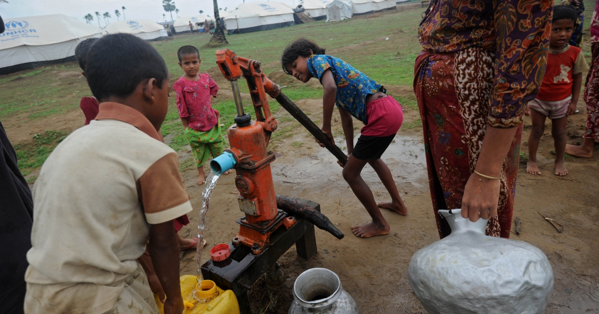 Rohingya children pump water at the Ohnedaw Internally Displaced Persons (IDP) camp on the outskirts of Sittwe on May 15, 2013.</p>