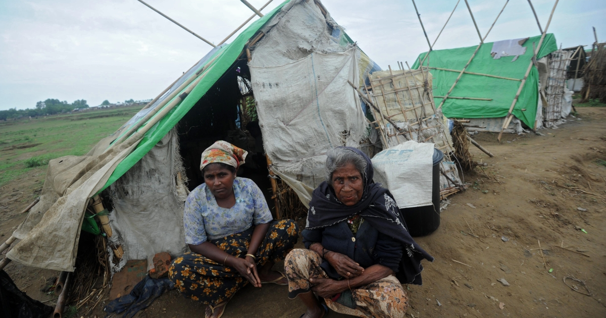 Rohingya women sit in front of their relief tent at the Mansi Internally Displaced Persons (IDP) camp on the outskirts of Sittwe on May 15, 2013.</p>