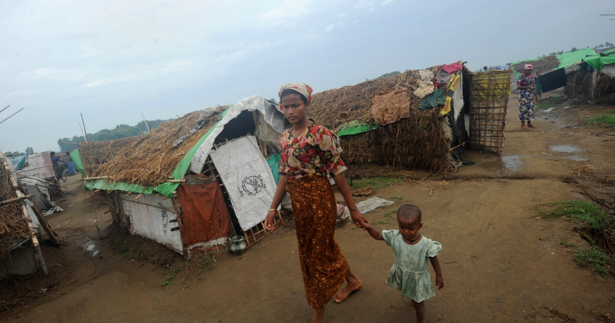 A Rohingya woman and her child walk in front of tents at the Mansi Internally Displaced Persons (IDP) camp on the outskirts of Sittwe on May 15, 2013.</p>