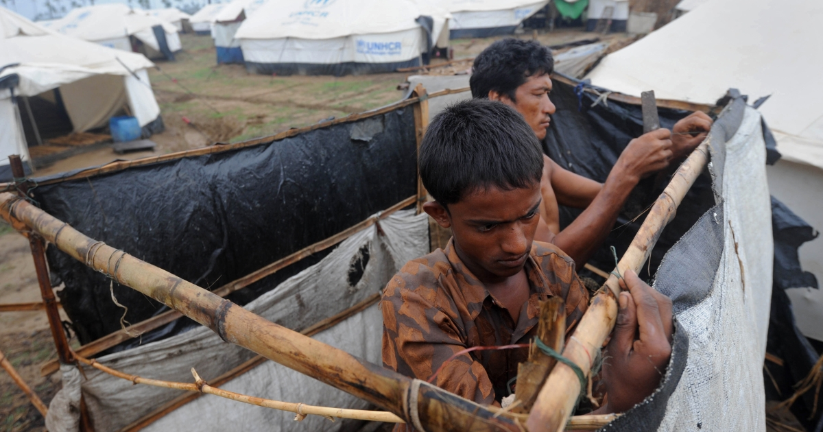 A Rohingya man fixes his tent at the Ohnedaw Internally Displaced Persons (IDP) camp on the outskirts of Sittwe on May 15, 2013.</p>