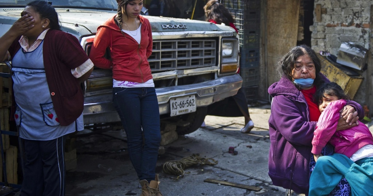 Local residents gather outside their homes severely damaged or destroyed in the gas tanker explosion on the outskirts of Mexico City on May 7, 2013. The Mexico State government has promised to help those affected rebuild their lives.</p>