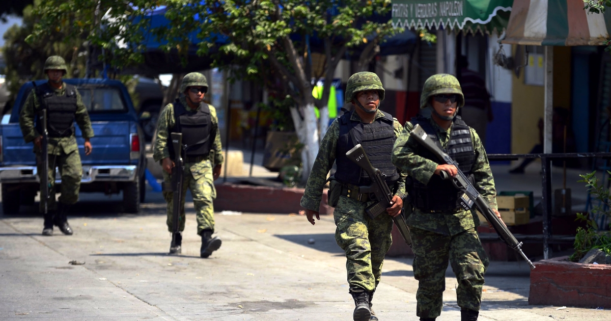 Mexican army soldiers patrol the streets of Buenavista Tomatlan in criminal