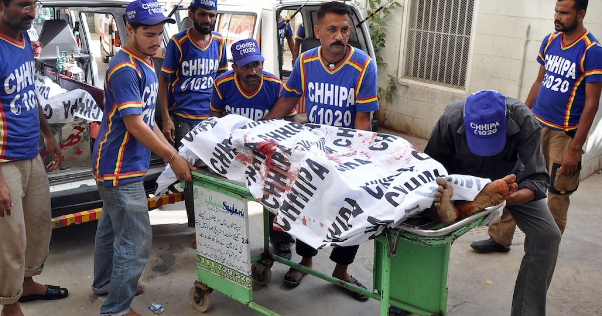 Pakistani volunteers move the dead bodies of the boy's kidnappers to a hospital in Karachi on May 27, 2013.</p>