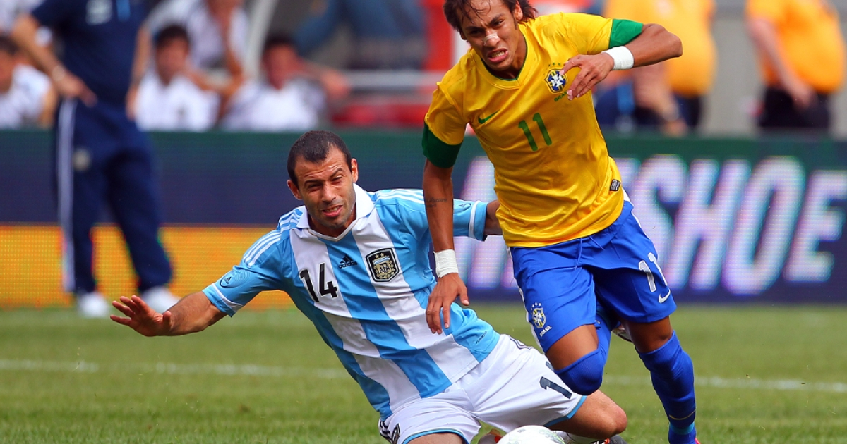 Javier Mascherano #14 of Argentina makes a slide tackle on the ball controlled by Neymar #11 of Brazil during the second half of an international friendly soccer match on June 9, 2012 at MetLife Stadium in East Rutherford, New Jersey.</p>