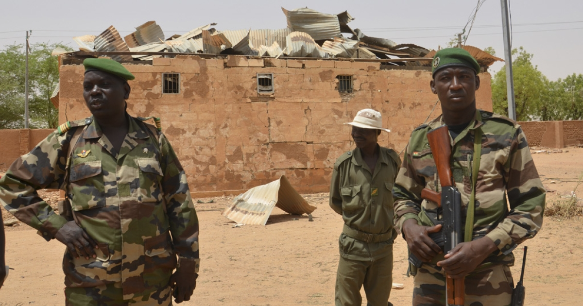 Nigerien soldiers stand near a damaged building at an army base in Agadez on May 26, 2013. Militants linked to Al Qaeda staged twin bombings at the base on May 23. In all, the attack claimed 24 victims and eight militants, according to Niger's Defence Minister.</p>