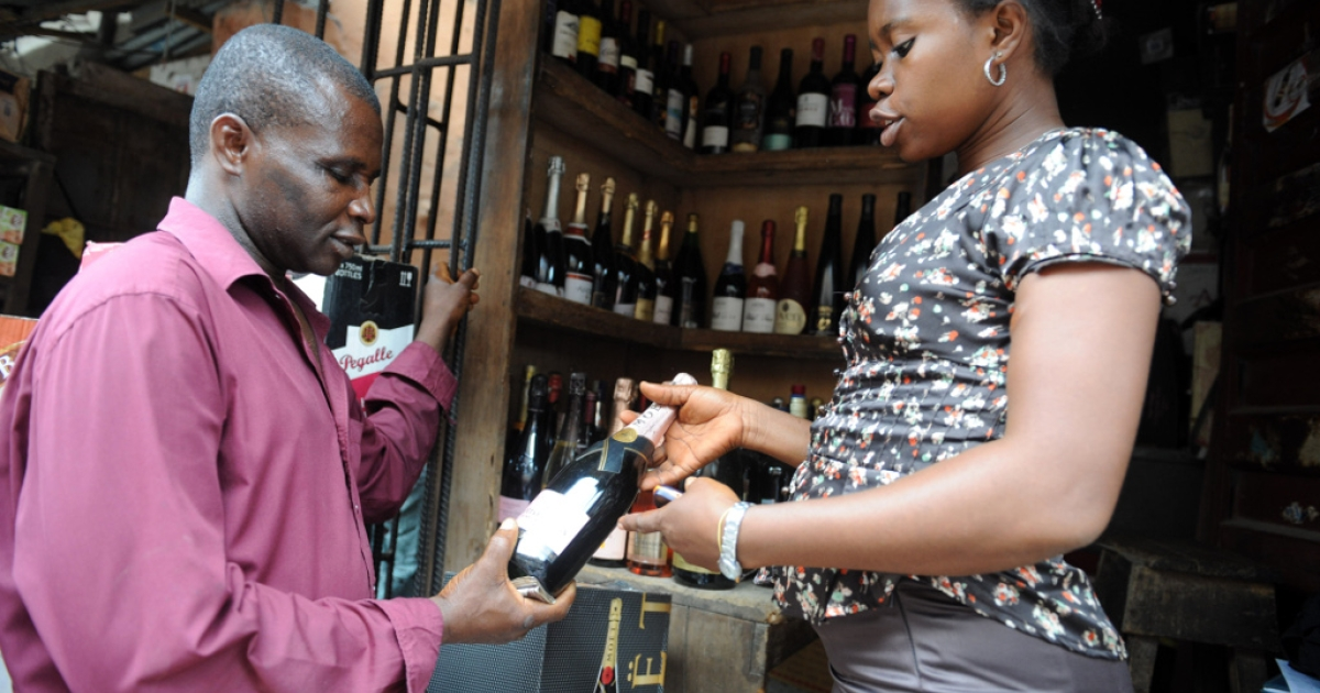 A sales attendant shows a bottle of champagne to a customer at a roadside shop in Lagos, Nigeria on April 23, 2013.</p>