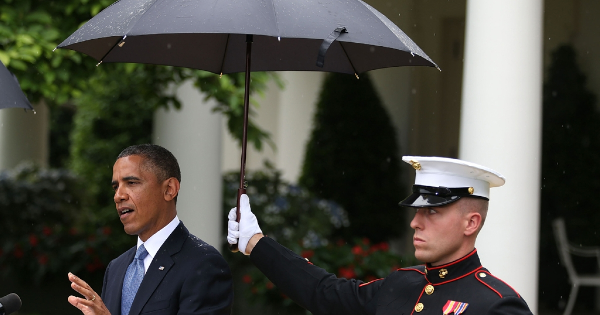 A US Marine holds an umbrella over President Barack Obama as he and Prime Minister Recep Tayyip Erdogan of Turkey (not shown) speak to the media in the Rose Garden at the White House May 16, 2013 in Washington, DC.</p>