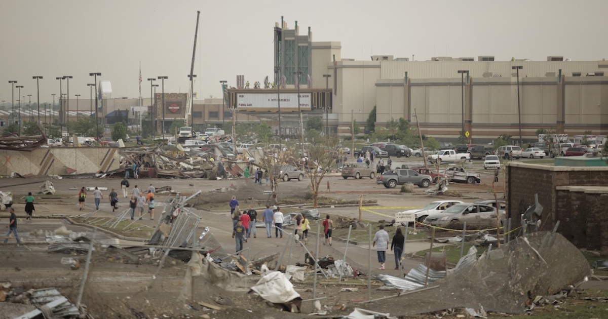 People walk through a damaged area near the Moore Warren Theater after a powerful tornado ripped through the area on May 20, 2013 in Moore, Oklahoma.</p>