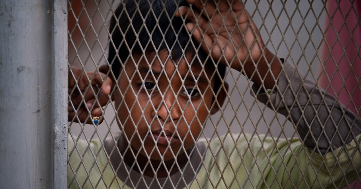 In this photograph taken on April 8, 2013, a young Myanmar Muslim Rohingya refugee looks on behind a wired fence at Indonesia's Belawan immigration detention center in Medan city located on Sumatra island, where eight Myanmar Buddhist detainees were killed by Myanmar Muslim Rohingya refugees inside the detention center on April 5, 2013. Some 200 asylum seekers, from countries including Sri Lanka and Afghanistan as well as Myanmar, remain at the detention center in the port town of Belawan, with some rooms holding large groups. They have been badly shaken by the killings.</p>