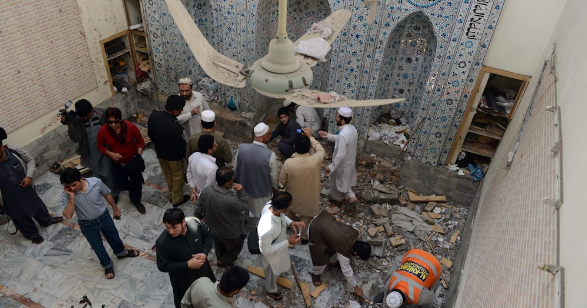 Local Pakistani residents and volunteers inspect a mosque following a bomb explosion in Peshawar on March 9, 2013.</p>