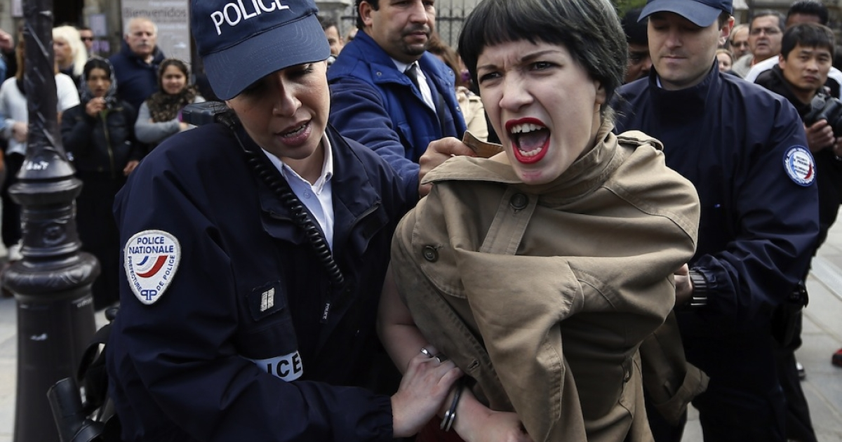 A member of the FEMEN feminist activist group is arrested by police in Paris, on May 22, 2013.</p>