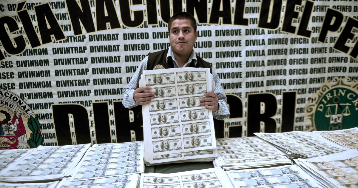A Peruvian policeman shows printed sheets of counterfeit US $100 bills.</p>