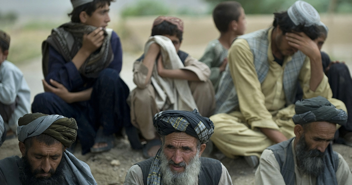 Afghan residents watch a patrol by US Army soldiers from Delta Company at Qalacha village in Kandahar on Sep. 10, 2012.</p>