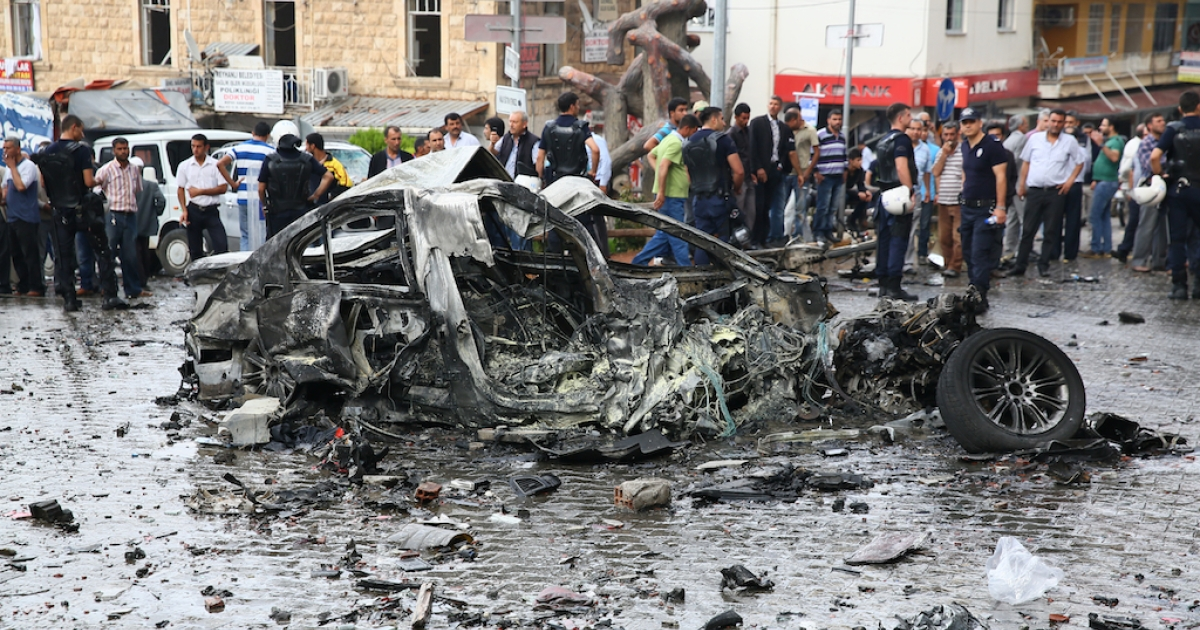 A crowd gathers around the wreckage of a car bomb in the central shopping district of the Turkish town of Reyhanli. Two car bombs killed at least 40 people and wounded more than 100 in Reyhanli on the Syrian border on Saturday. The bombs, which exploded in downtown Reyhanli, including outside the local municipal building, raised fears that Syria's ongoing civil war is spilling over its borders.</p>