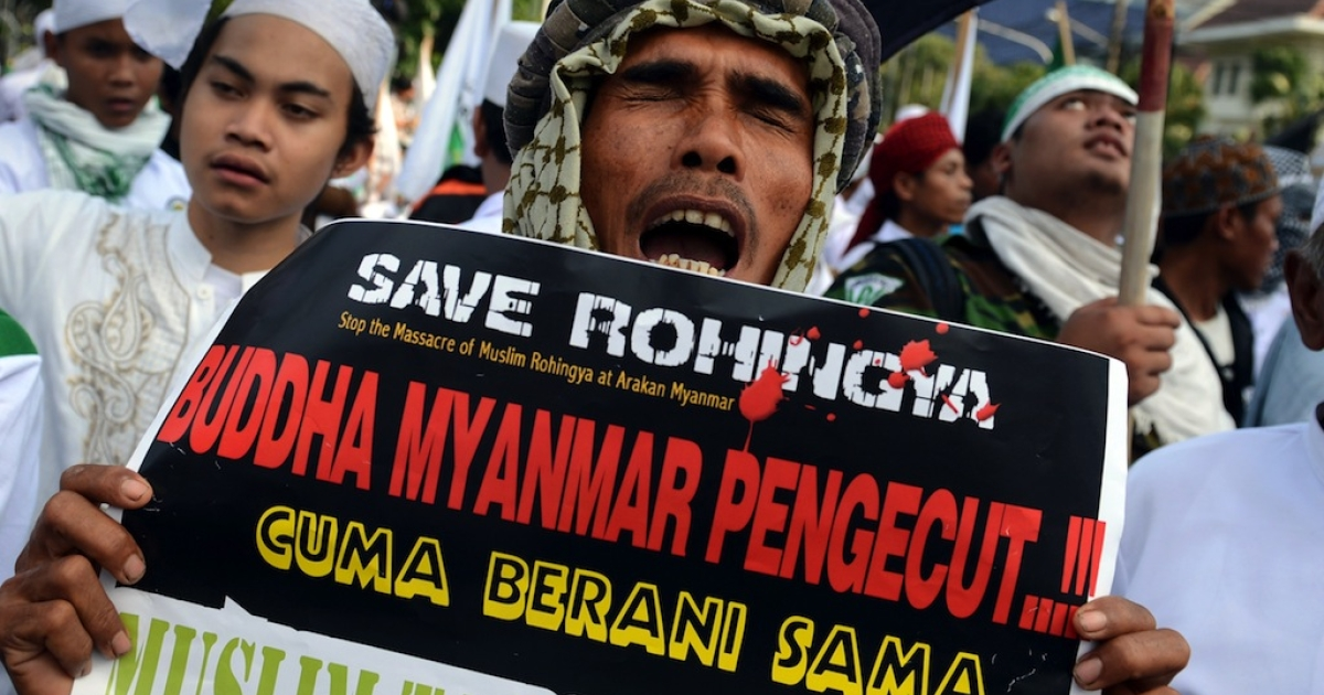 A protester of the Islamic Defenders Front (FPI) holds a placard calling to 'stop the massacre of Muslim Rohingya and Myanmar Buddhists cowards' in Jakarta on May 3, 2013.</p>