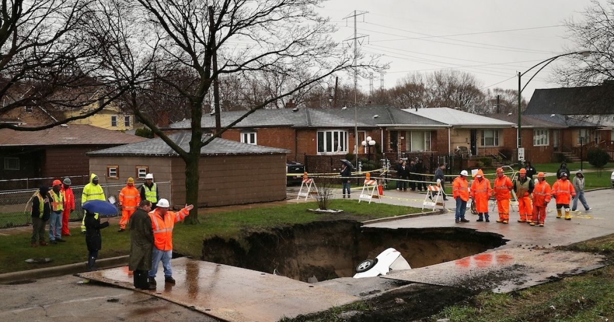 Workers prepare to pull vehicles from a sinkhole that opened up on a residential street in the South Deering neighborhood on April 18, 2013 in Chicago, Illinois.</p>