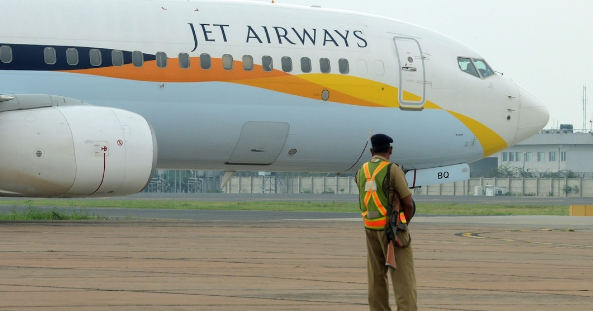 An Indian security official looks on as an aircraft of Jet Airways taxies after landing in New Delhi. A Jet Airways Airbus A330-200 carrying 300 guests of the wealthy Gupta family landed at South Africa's main military base earlier this week, sparking an uproar over the family's ties to the South African president.</p>