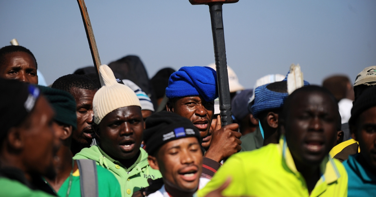 Striking Lonmin mine workers dance and sing as they gather May 15 at the Wonderkop stadium in Marikana during a strike.</p>