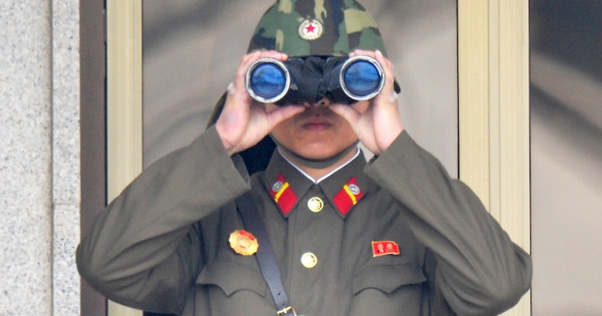 A North Korean soldier watches from his quarters at the truce village of Panmunjom in the demilitarised zone on April 23, 2013.</p>