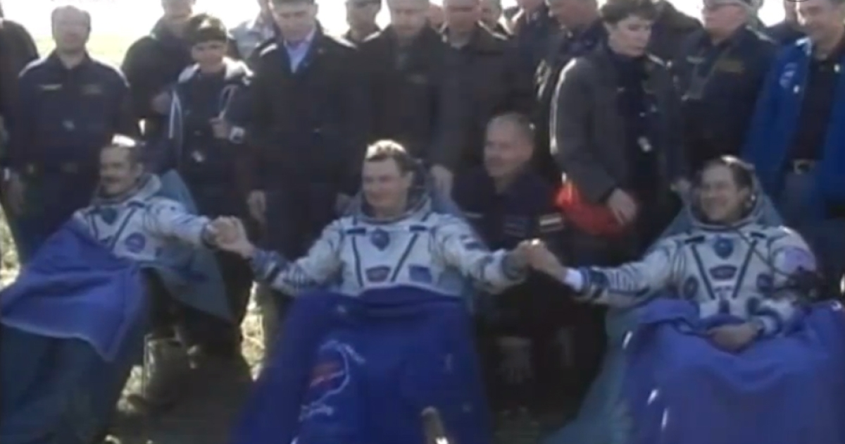 The Expedition 35 crew members are assisted by recovery teams and medical personnel shortly after landing in Kazakhstan aboard their Soyuz TMA-07M spacecraft. Credit: NASA TV</p>