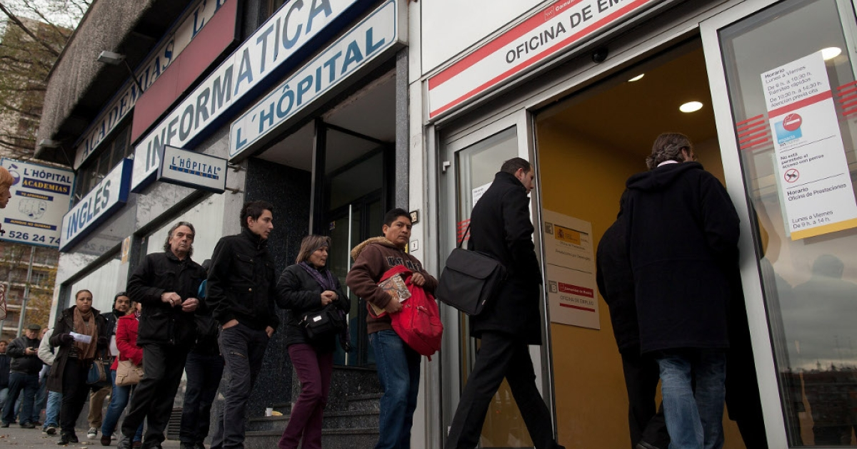 People line up to enter a government employment office as it opens on December 4, 2012 in Madrid.</p>