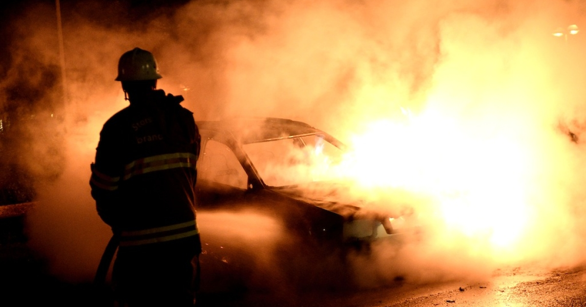 Firemen extinguish a burning car rioters set on fire in Kista, Stockholm on May 21, 2013.</p>