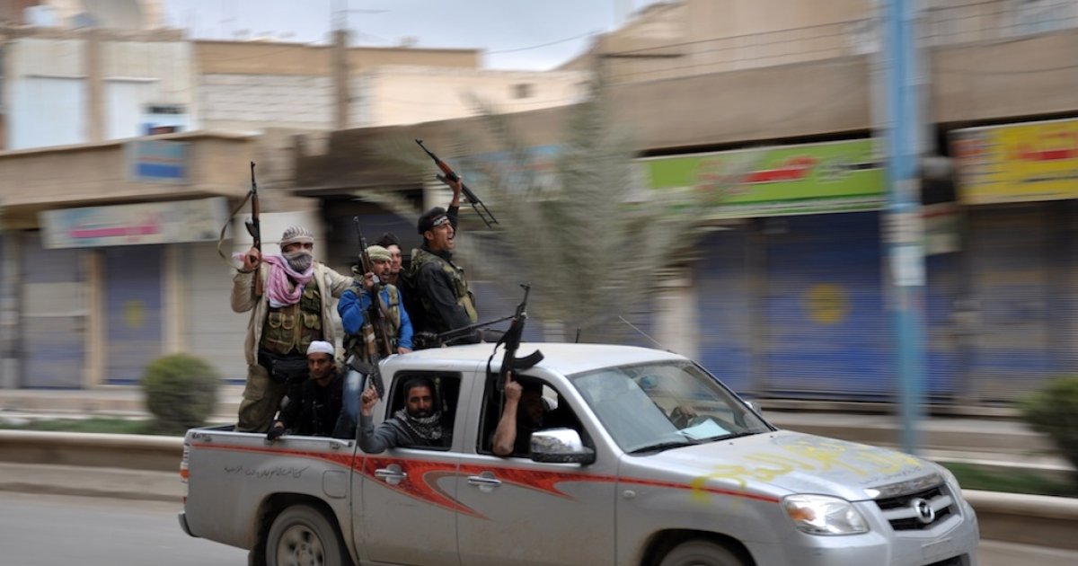 Rebels celebrate in a street in the northern Syrian city of Raqqa after capturing the city on March 4, 2013.</p>