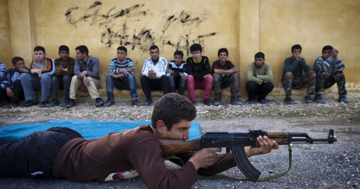 Syrian youth Sobhi, 15, holds an AK-47 assault rifles as he takes part in a military training on January 23, 21013 at a former school turned into a 'military academy' in Tlaleen in the northern Syria's Aleppo province.</p>