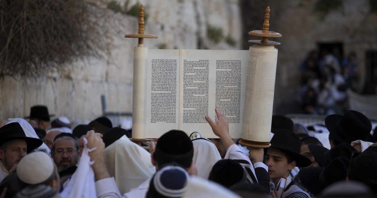 A Jewish man raises Torah scrolls during the Cohanim prayer (priest's blessing) during the Pesach (Passover) holiday at the Western Wall in the Old City of Jerusalem on March 28, 2013.</p>