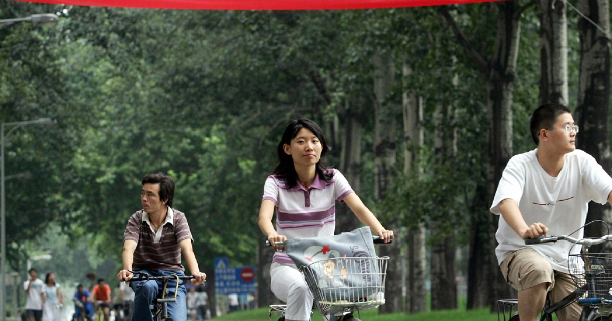 Chinese university students cycle on the campus of Tsinghua University in Beijing.</p>