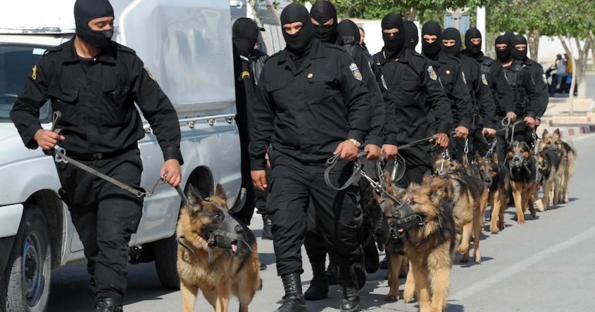Tunisian Police Special Unit agents patrol with dogs in a street that leads to Okba Ibn Nafaa mosque in the southern Tunisian city of Kairouan on May 19, 2013. Tunisian Salafist movement Ansar al-Sharia called on its supporters to gather in a Tunis suburb, after the government banned it from holding its annual congress in the central city of Kairouan.</p>