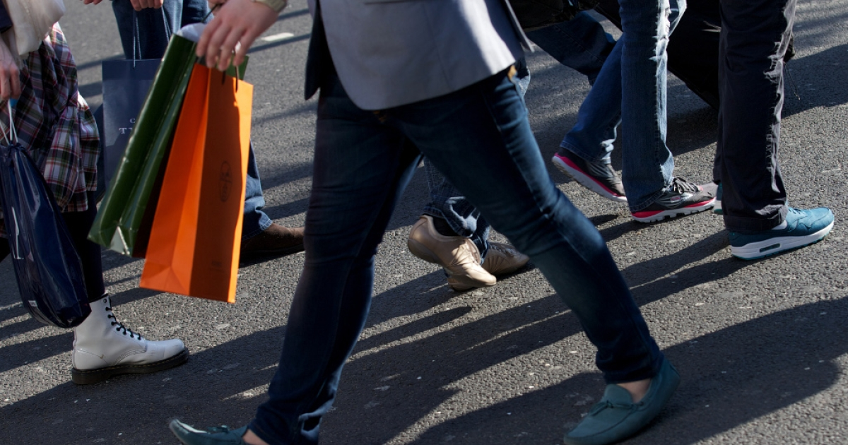 Shoppers carry their purchases as they walk along Oxford Street in central London on April 25, 2013.</p>