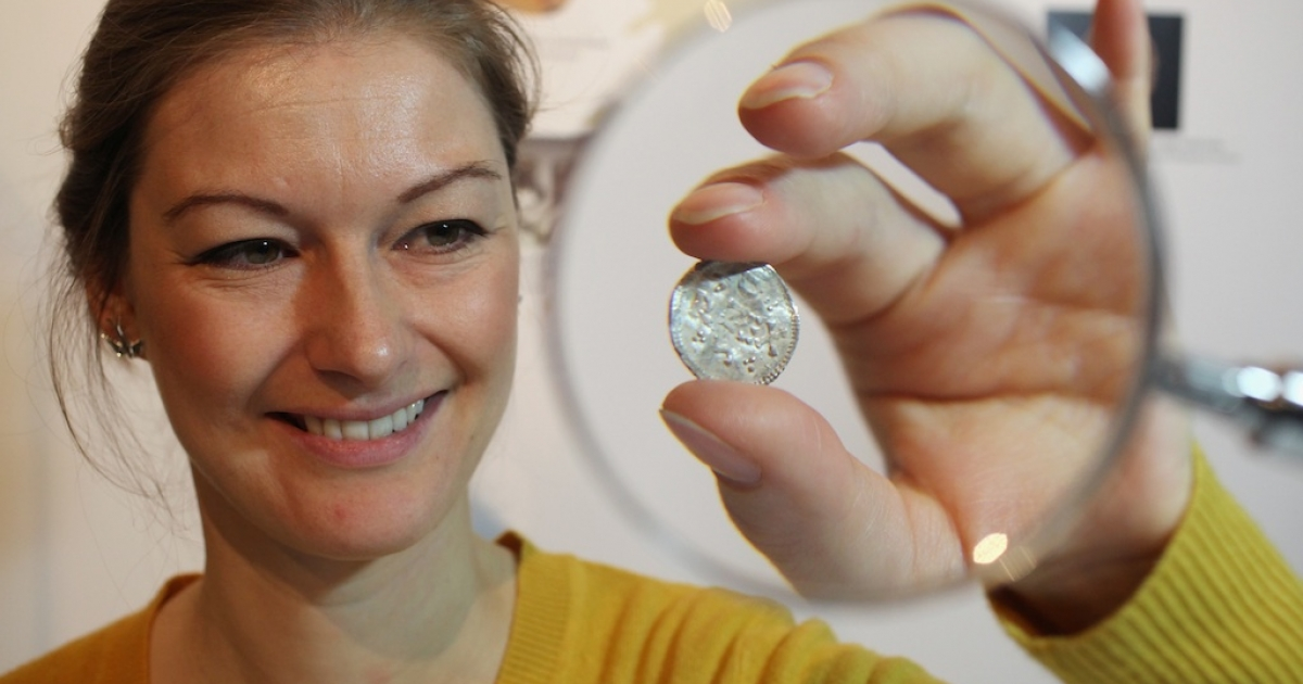 An employee of the British Museum examines a silver coin dating from 900 AD which is part of the Silverdale Viking Hoard on December 14, 2011 in London, England. The picture does not depict the latest group of Viking coins found last year by a Danish teen in Denmark.</p>