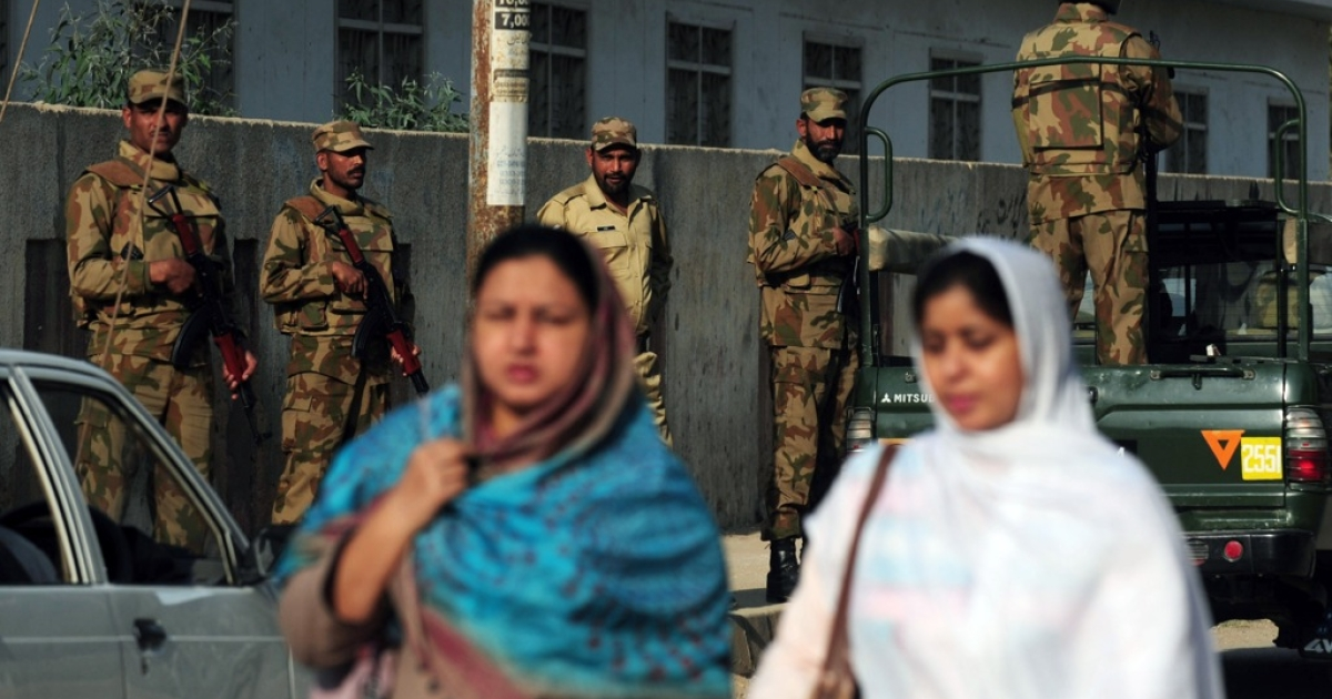 Pakistani women walk past as Pakistani army soldiers stand guard during a door-to-door voter verification campaign in Karachi on Jan. 29, 2013. The door-to-door verification of voters in Karachi was ordered by the Supreme Court after complaints about irregularities in enrollment of about three million people for the upcoming election.</p>